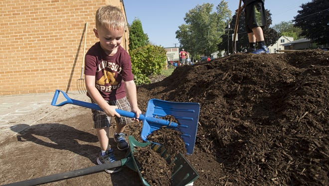 Masen Kohfeldt, 3, uses his miniature shovel to fill another shovel while doing yard work Saturday, Sept. 23, 2017, around South Park Middle School as part of Project CURB.