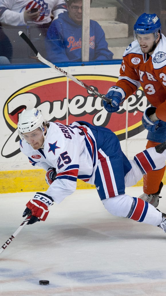 The Amerks' Mikhail Grigorenko, left, reaches for the puck after being checked by Syracuse's Dalton Smith in the second period.