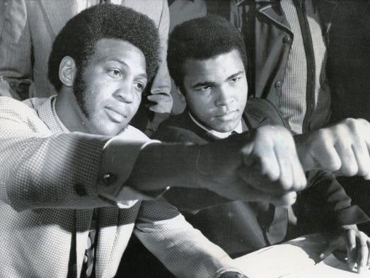 Jimmy Ellis, left, former World Boxing Association Champion, and Muhammad Ali, former world heavyweight king, stretch out clenched fists as they signed in New York for a 12-round bout at the Houston Astrodome in 1971.