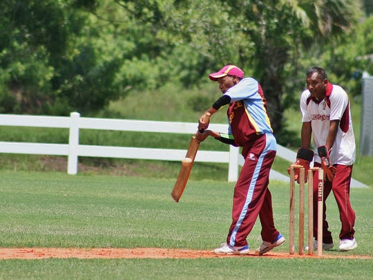 A batter from Fort Lauderdale's Berbice Cricket Club connects during the quarterfinal game at Veterans Park on Sunday. Wicket keeper Kemraj Singh of Lehigh Cricket Club watches the hit unfold.