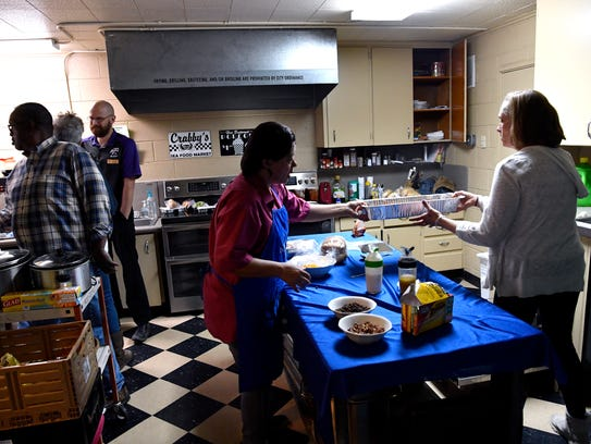 Students and staff clean up in the FaithWorks kitchen after lunch April 10.