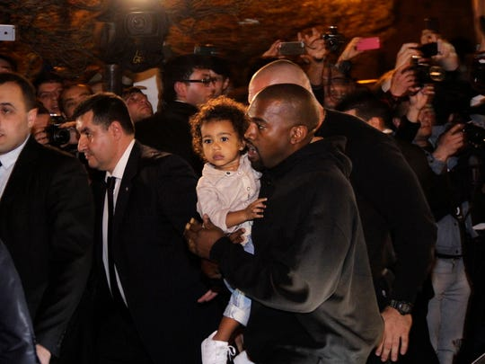 Kanye West carries North West as they arrive at a hotel