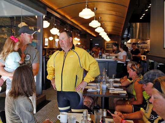 Nate Kaeding held his daughter Tess, 2, as she talked with then-RAGBRAI director T.J. Juskiewicz during breakfast at Pullman Bar and Diner as the RAGBRAI pre-ride team rolled through Iowa City on June 6, 2015.