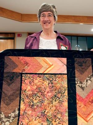 Las Colcheras Quilt Guild member Susan Truitt displays her custom designed quilt, Autumn Splendor.