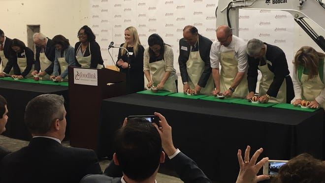 """Officials take part in the ceremonial """"apple slicing"""" at Wednesday's groundbreaking celebration at Foodlink. The new Community Kitchen is scheduled to be completed by Fall 2016."""