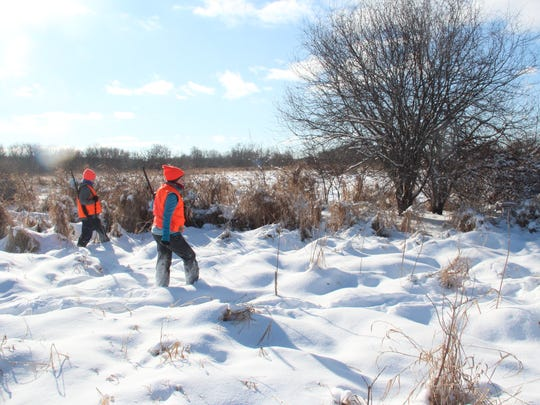 Casey Scott-Weathers, left, and Kimbrin Cornelius, both of Madison, walk through a snow-covered field near Cottage Grove during a Learn To Hunt for Food program. Together with a mentor, the novice hunters were in search of cottontail rabbits.