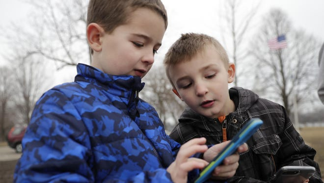 Jacob Mathis, left, 7, of Appleton, and Michael Fredrick, 6, of Oshkosh, play Pokemon Go on Feb. 20 at Kimberly Point Park in Neenah. Warm weather combined with Pokemon Go's addition of 80 new kinds of creatures available for people to catch on Feb. 17 is bringing crowds to Kimberly Point Park to play the popular game.