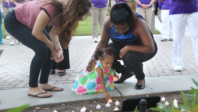 Pitts family friend Aliyah Solis, left, watches as Michelle Burgess, right, helps 15-month-old A'Ziah Kelly place a candle near a memorial to grandmother, murder victim  Dorla Pitts,  Wednesday in Fort Myers. A'Ziah's parents, Starlette Pitts and Michael Kelly Jr, were victims of an August triple homicide in Lehigh Acres.
