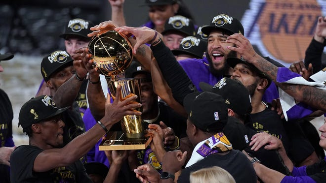 The Los Angeles Lakers players celebrate after the Lakers defeated the Miami Heat 106-93 in Game 6 of the NBA Finals on Sunday in Lake Buena Vista, Fla.