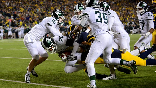 Jalen Watts-Jackson (20) crosses the goal line to score the winning touchdown after time expired to claim the win and the Paul Bunyan trophy for Michigan State in a 27-23 over Michigan Saturday, October 17, 2015, at Michigan Stadium in Ann Arbor. Watts-Jackson recovered a muffed punt for a touchdown.