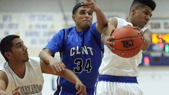 San Elizario's Jevon Caster, right, comes down with a defensive rebound against Saul Meza, center, of Clint on Tuesday night at San Elizario. At left is Eddie Conde of San Elizario.