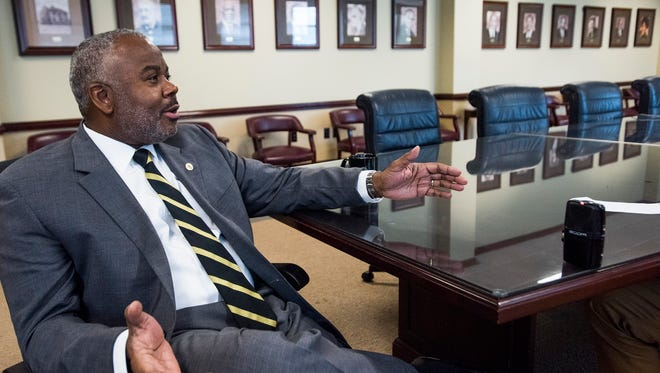 New Alabama State University President Quinton Ross talks on the ASU campus in Montgomery, Ala., on Wednesday October 11, 2017. Photographers of previous ASU presidents line the wall behind Ross.