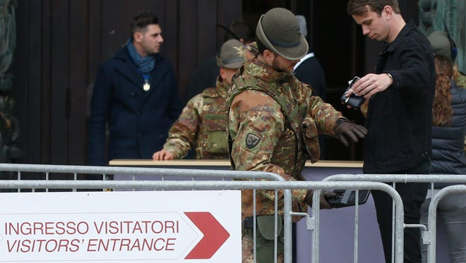 Italian soldiers check visitors at the entrance of the Duomo gothic cathedral in Milan, Saturday, Nov. 14, 2015. Italy's top security official says Italy has heightened security inside Italy and along its borders, especially with France, following the attacks in Paris. Interior Minister Angelino Alfano told reporters after meeting with Premier Matteo Renzi and other top security and intelligence officials that the country had raised its alert level to the second highest, allowing for rapid deployment of special forces if necessary. (AP Photo/Luca Bruno)