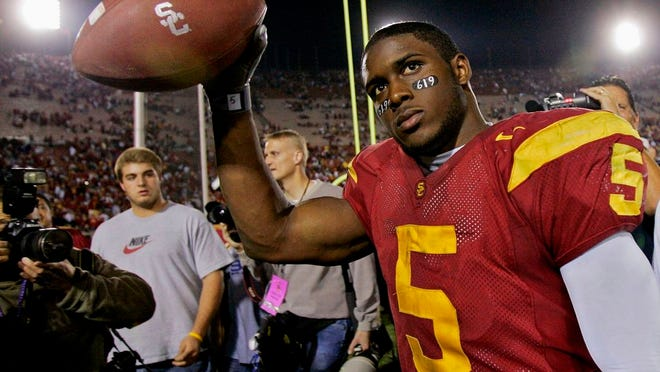 "From Nov. 19, 2005, Southern California tail back Reggie Bush walks off the field holding the game ball after the Trojans defeated Fresno State, 50-42, at the Los Angeles Coliseum. The former star running back had been prohibited from interacting in an official capacity with the school he played for from 2003-05 since NCAA sanctions handed down in 2010. Bush and USC were penalized for him and his family receiving impermissible benefits while he was still in school. USC President Carol Folt wrote in a letter to Bush on Wednesday, June 10, 2020, that he could now ""be afforded the privileges and courtesies extended to all Trojan football alums."""