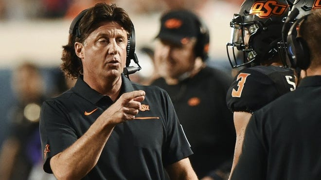 Oklahoma State head coach Mike Gundy points to his staff on the sidelines during the first half of an NCAA college football game against Kansas State, in Stillwater, Okla., Saturday, Sept. 28, 2019.