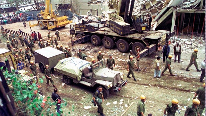 In this Sunday, Aug. 9, 1998 file photo, Israeli soldiers bring in heavy lifting equipment to the wreckage of the Ufundi House, adjacent to the U.S. embassy in Nairobi.