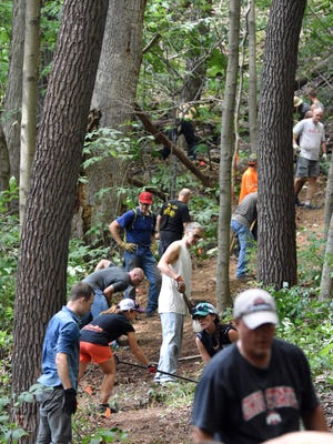A group works on a 100-yard section of trail to prepare it for International Mountain Bicycling Association standards Saturday at Great Seal State Park.