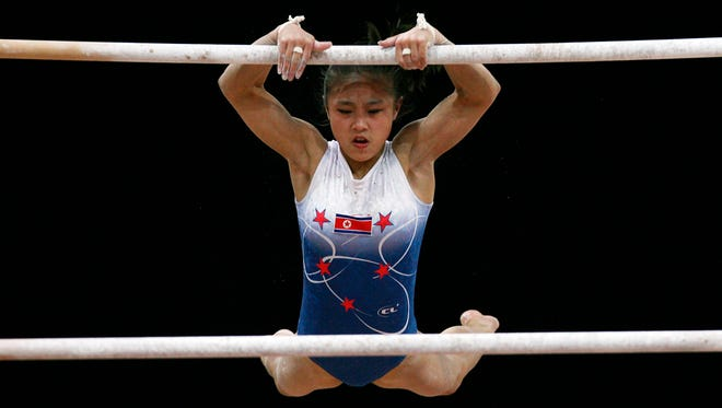 In this Dec. 3, 2006, file photo, North Korea's Cha Yong Hwa performs on the uneven bars during the Asian Games gymnastics women's team final at the 15th Asian Games in Doha, Qatar. Cha was banned Sept. 17, 2014, by the International Gymnastics Federation and stripped of all her results since 2006 in a case of age cheating.