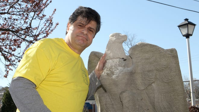 White Plains native Joe Giglio stands next to his newly sculpted eagle head that he installed on the city's World War I monument.