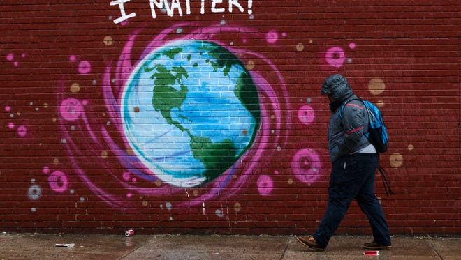 A pedestrian is pictured walking past an Earth Day mural in Philadelphia.