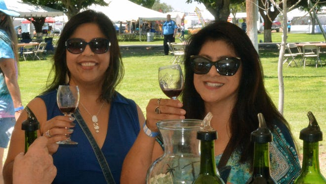 Claudia Hernandez, left, and Alma Hernandez enjoy a glass of Viva la Roja at the New Mexico Harvest Wine Festival on Sunday, Sept. 4, 2016.