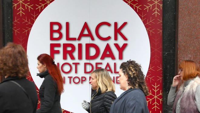 Shoppers pass a store Friday, Nov. 24, 2017 in London, Britain.
