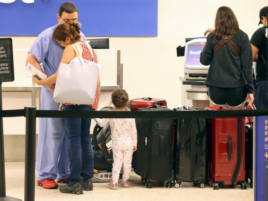 General surgeon Michael Reyes (left) hugs his wife Sara Reyes (center) as she prepares to flight out of Corpus Christi with her daughter Eva Reyes (right) and he prepares to stay as Hurricane Harvey approaches the Gulf Coast area on Friday, Aug. 25, 2017, at the Corpus Christi International Airport in Corpus Christi.