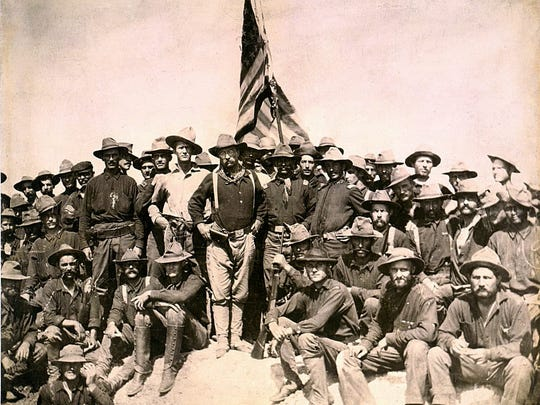 "Theordore ""Teddy"" Roosevelt (center, below the flag)"