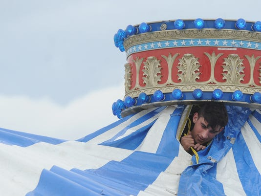 J.P. Louw with Majestic Midways pops his head up from under the tent to set up the carousel at the York Expo Center on Friday, April 3, 2015. The crew was setting up rides for the York County Spring Carnival, which runs on the weekends of April 10 and April 17.