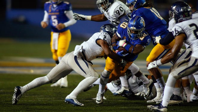 SJSU running back Malik Roberson is tackled by Nevada's Asauni Rufus on Saturday.