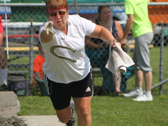 Debra Brown releases a horseshoe during a competition