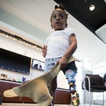 Miyah Williams, 3, holding her old prosthesis, shows her new one she's wearing, at the Newseum in Washington, D.C., where they are attending a meeting on the pediatric device problem hosted by the Children's National Medical Center. Miyah is an above-the-knee amputee who struggled with a painful and hard-to-move socket attaching her prosthesis until last August, when she received a new child-sized kind. Miyah's old prosthesis lays on the floor.