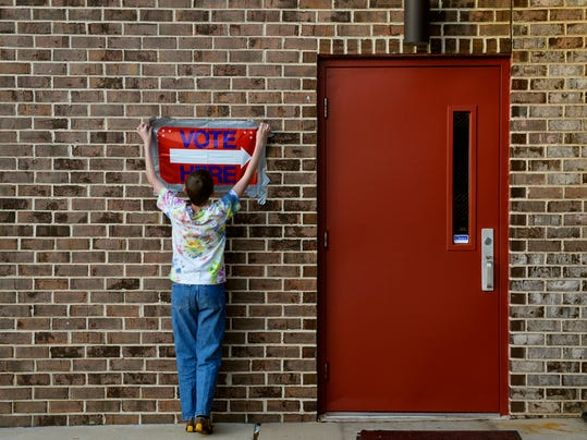 """Jonathan Cunnings, 12 of Dallastown, re-affixes a """"VOTE HERE"""" sign outside the polling place at Dallastown Fire Company during last year's election."""
