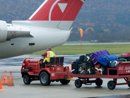 Wednesday and Sunday are anticipated to be the heaviest travel days during the Thanksgiving weekend. Luggage is brought to a waiting plane at Elmira Corning Regional Airport in this file photo.