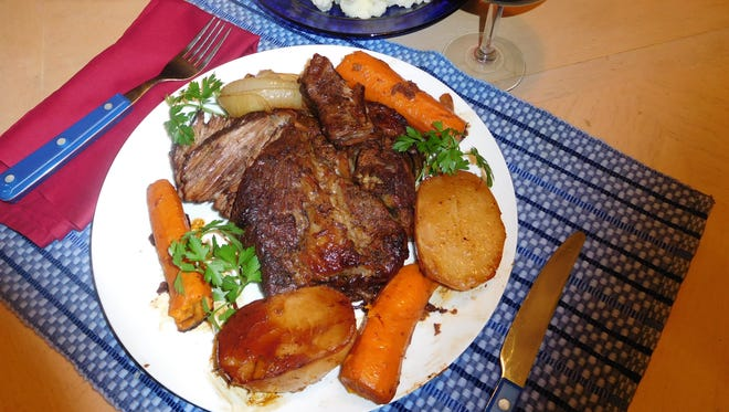 Beef pot roast served with carrots, onions and potatoes.