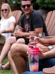 Patrons of Three Brothers Wineries and Estates in Geneva enjoy wine slushies outdoors July 15.