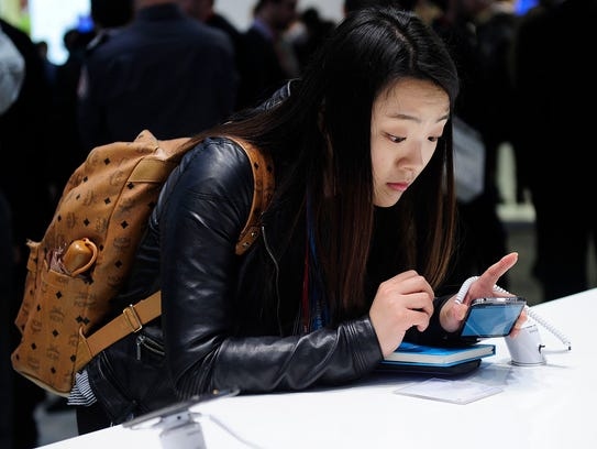 A visitors looks at a Samsung Galaxy S4 at the Mobile World Congress in Barcelona, on February 24, 2014. Many apps that turn your smartphone camera in to a search engine are available for Android and iPhones.