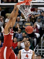 Alabama's Galin Smith (30) dunks in front of Virginia Tech's Nickeil Alexander-Walker (4) during the first half of an NCAA men's college basketball tournament first-round game Thursday, March 15, 2018, in Pittsburgh. (AP Photo/Keith Srakocic)