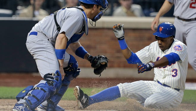 The Mets' Curtis Granderson (3) slides across home plate ahead of the tag from Los Angeles Dodgers catcher A.J. Ellis scoring on a sacrifice fly to right by Eric Campbell during the second inning Thursday.