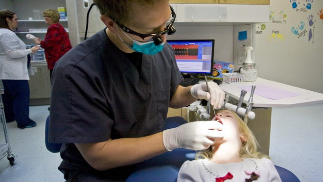 A dentist examines a child's teeth.