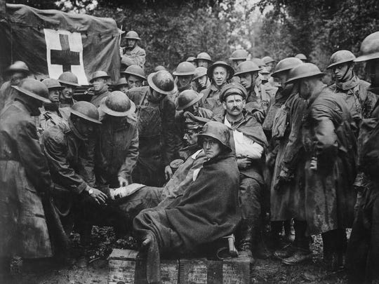 American troops help wounded German soldiers at Meuse-Argonne, France, following the armistice halting World War I.