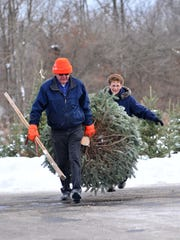 A couple drag a Christmas tree they cut Dec. 7 at Newby's Evergreen Farms in rural Wausau.