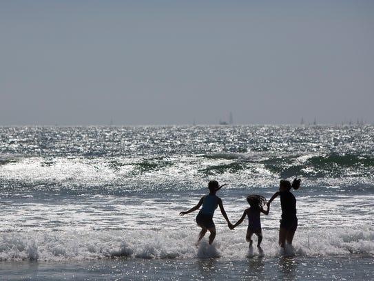 Beachgoers play in the break on Coronado Island in