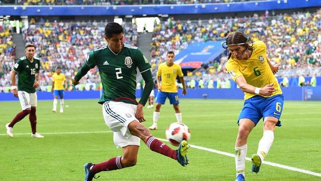 Brazil defender Filipe Luis in action against Mexico's Hugo Ayala.