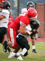 Damian Guck wraps up this running back during action