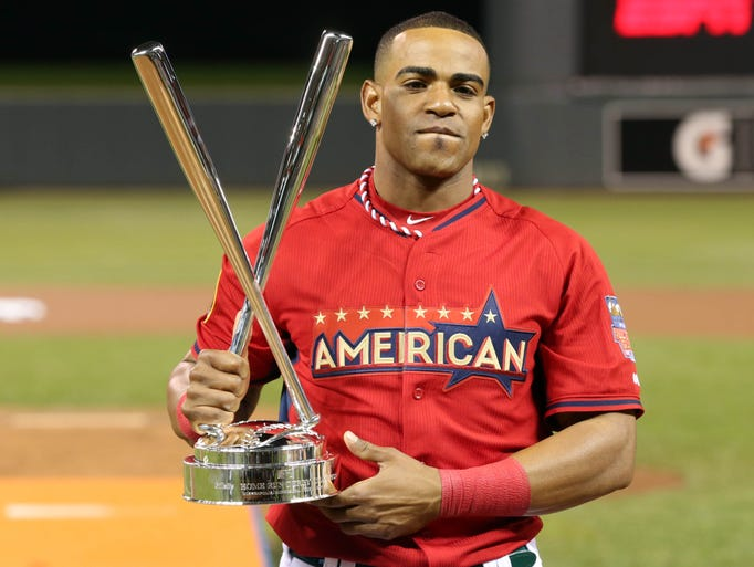 Yoenis Cespedes hoists the championship trophy after winning the 2014 Home Run Derby at Target Field.