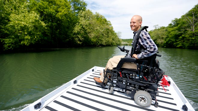Mark Grantham jokes with his dad as they float around Lake Springfield on a custom-designed home-built boat on Tuesday.