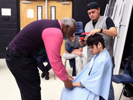 Moody High School teacher Wayne Bursey calms student BJ Ramirez, 17, as he gets his hair cut by Anthony Trevino, a barber with the Chop Shop, on Tuesday, Jan. 23, 2018, in preparation for the school's 15th annual Special Hearts Prom.