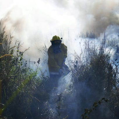 Guam Fire Department Firefighter Roland Alcantra douses grass to prevent flames from spreading near Talofofo Falls in April 2014.