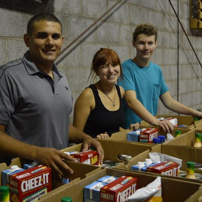 Cody Lamders, the youth pastor at First Baptist church in Belen, New Mexico, helps his students Savannah (17) and Aric (15) pack boxes at the Central Louisiana food bank on July 28.
